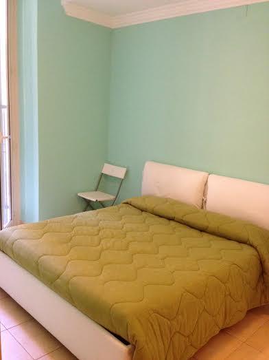 A cama de casal. Ao lado tem uma varandinha